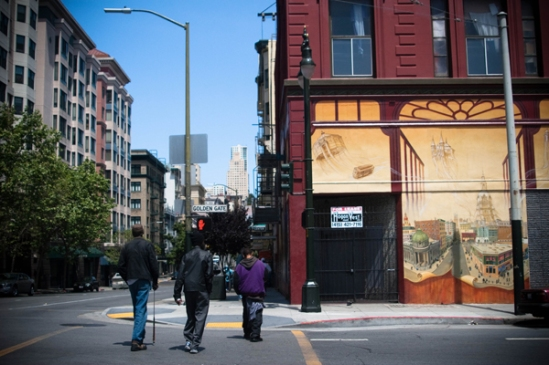 "A group of men walk by the ""Windows to the Tenderloin"" mural on Jones and Golden Gate created by artist Mona Caron, commissioned by the North of Market/ Tenderloin Community Benefit District. Photo by Nina Frazier"